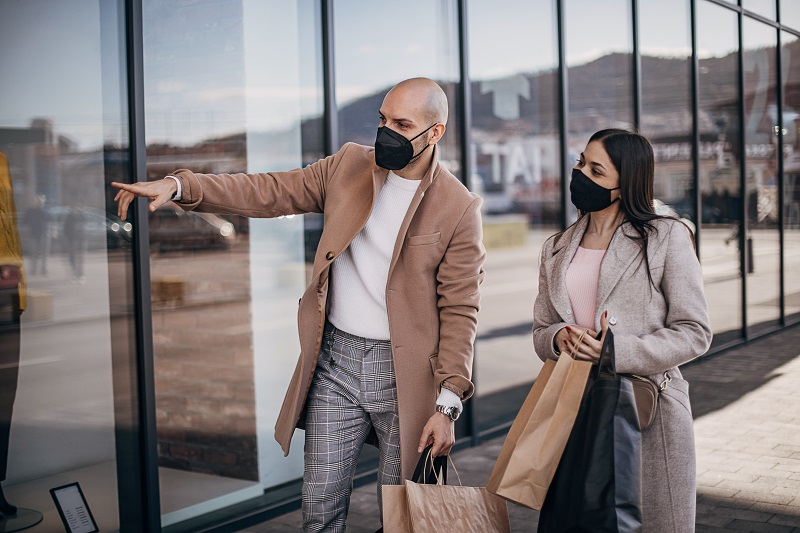 Young couple with protective face masks and shopping bags walking and enjoying shopping.