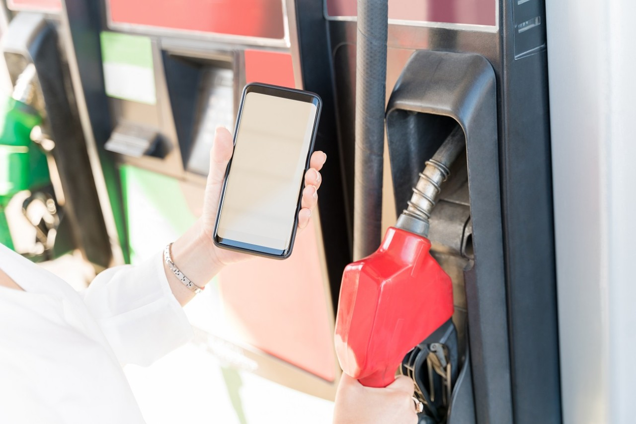 Cropped image of woman making payment through smartphone at self-service gas station