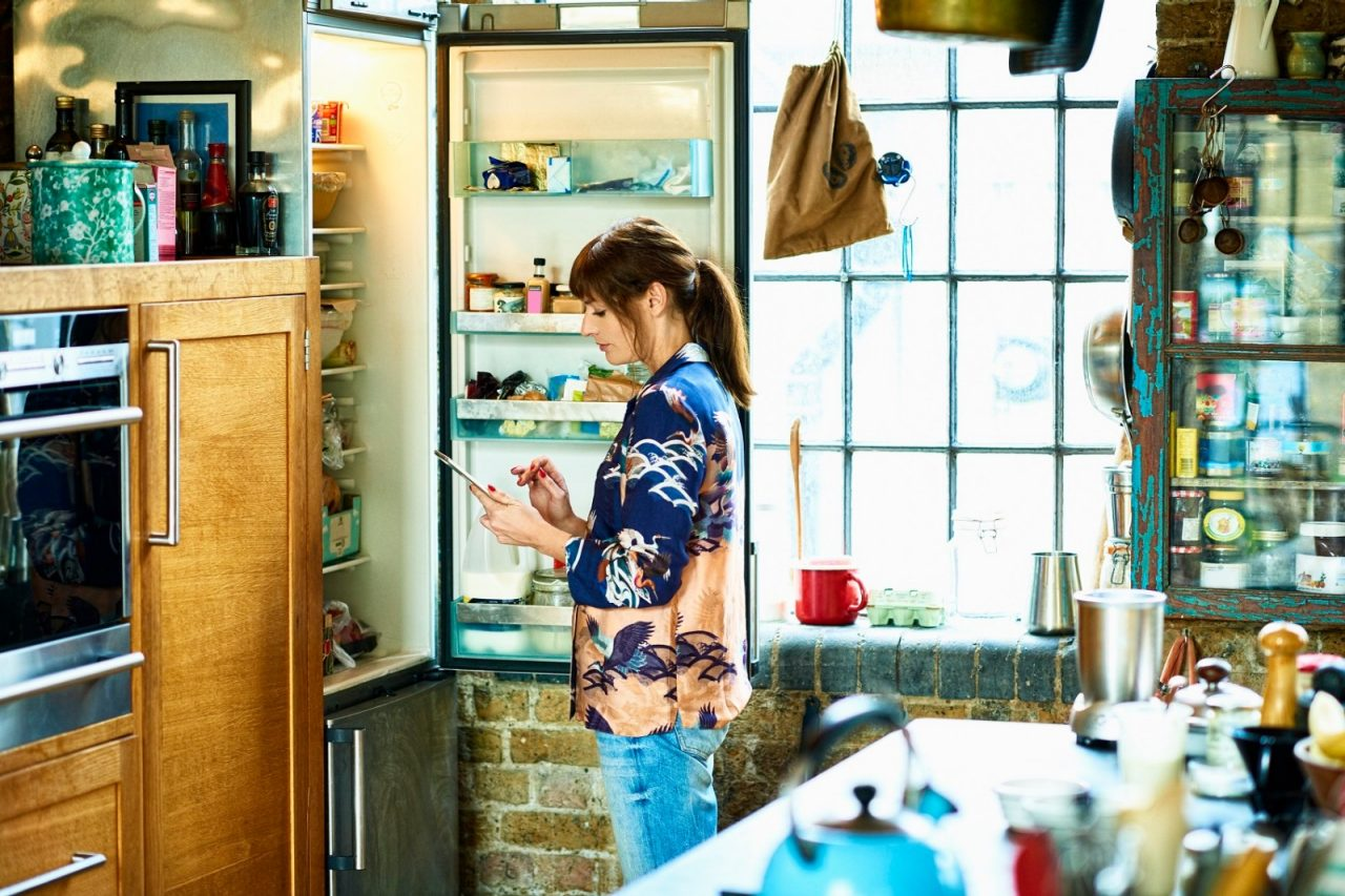 Mid adult woman using digital tablet in front of open refrigerator in kitchen