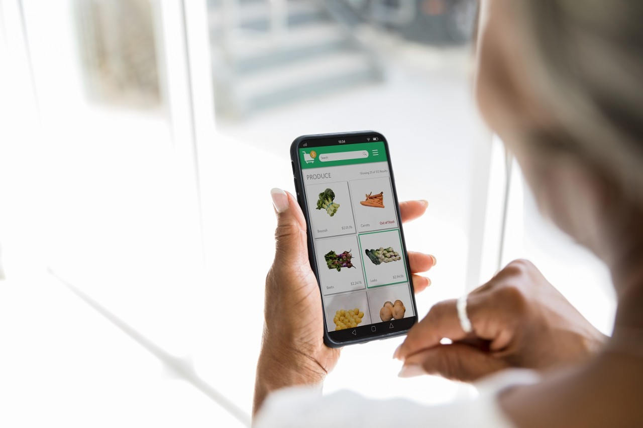 A woman uses a grocery delivery app on her smartphone. She is selecting fresh produce while using the app.