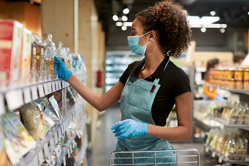 Supermarket and retail.One young supermarket employee sorting products on the shelfs