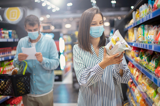 Two people protected from the Covid19 pandemic with face masks are buying some groceries in the supermarket. A woman is reading the ingredients from the backside of a product while in the background a man is checking his grocery list.