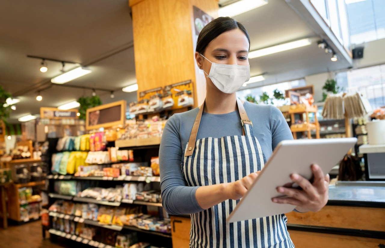 Woman working at a supermarket wearing a facemask while doing the stock inventory using a tablet computer - lifestyle concepts