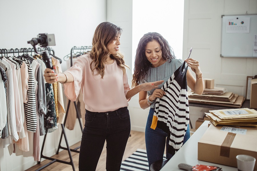 Working women at their store. They wearing casual clothing, accepting new orders online and taking photo of merchandise for customer or vlogging