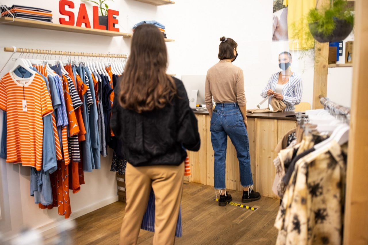 Rear view of people with face mask standing in a line with social distance at clothing store checkout counter. Customers with social distancing shopping in a fashion boutique after pandemic reopen.