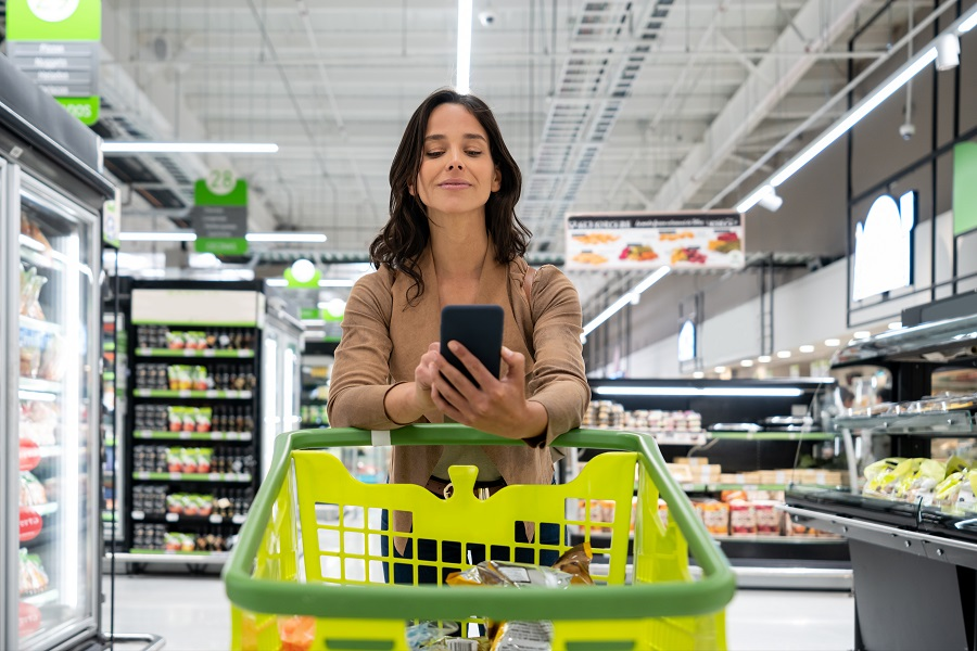 Cheerful young beautiful woman checking her shopping list on smartphone while leaning elbows on cart at the supermarket - Lifestyles