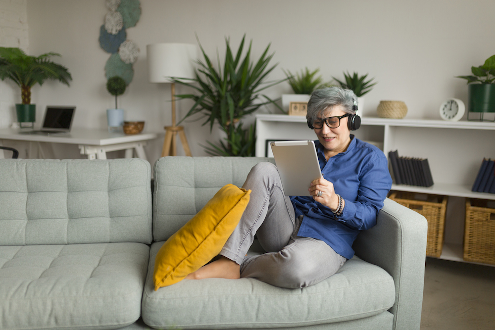 ältere frau sitzt zuhause auf dem sofa während sie onlineshopping