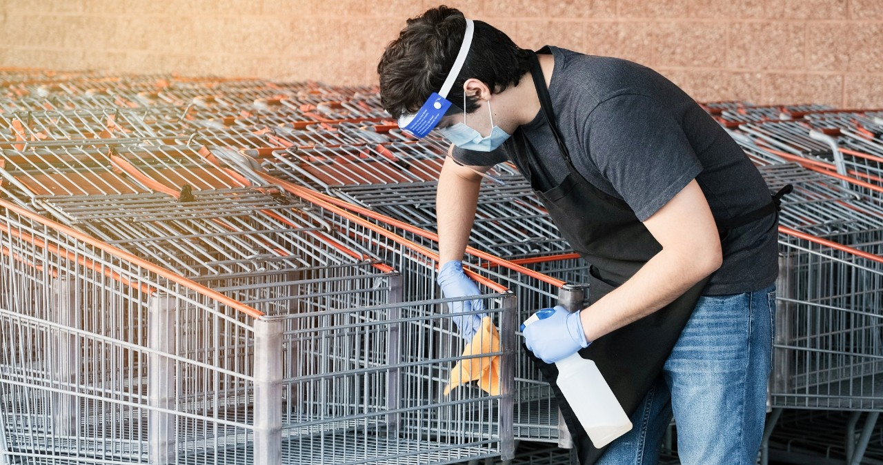 Supermarket employee wearing masks and latex gloves disinfecting shopping carts due contagion prevention