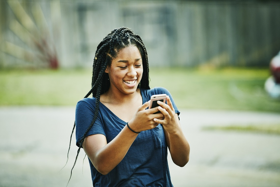 Laughing young woman looking at smartphone on summer evening