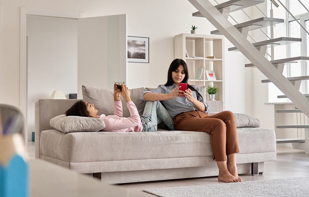Indian family mother with teen daughter using phones devices at home. Young mom with teenage child holding cellphones relaxing together on couch in living room. Social media technology addiction.