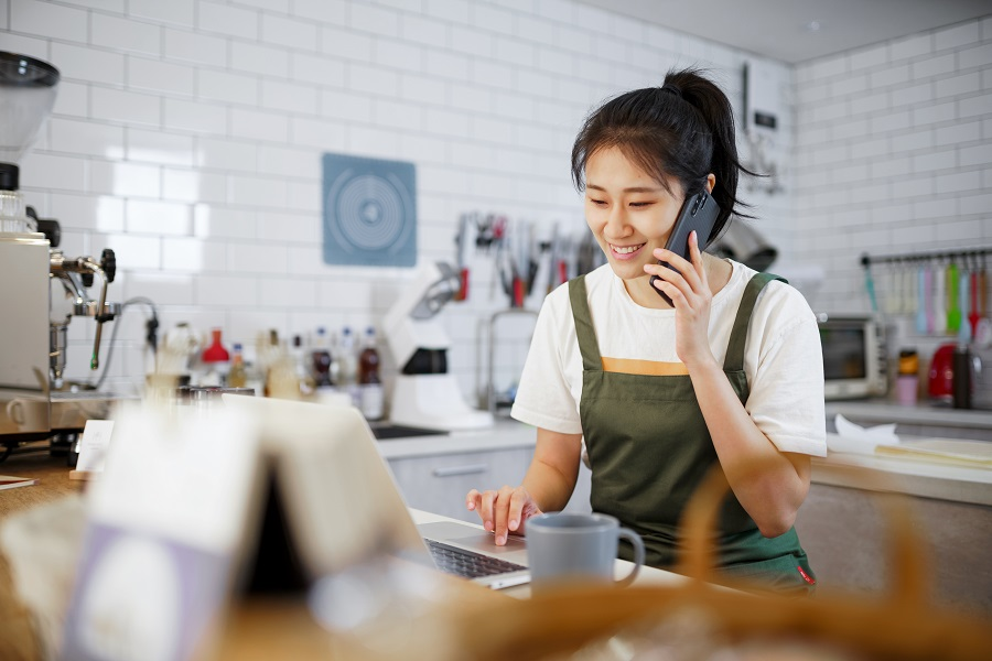 young chinese female Bakery business owner talking on cell phone