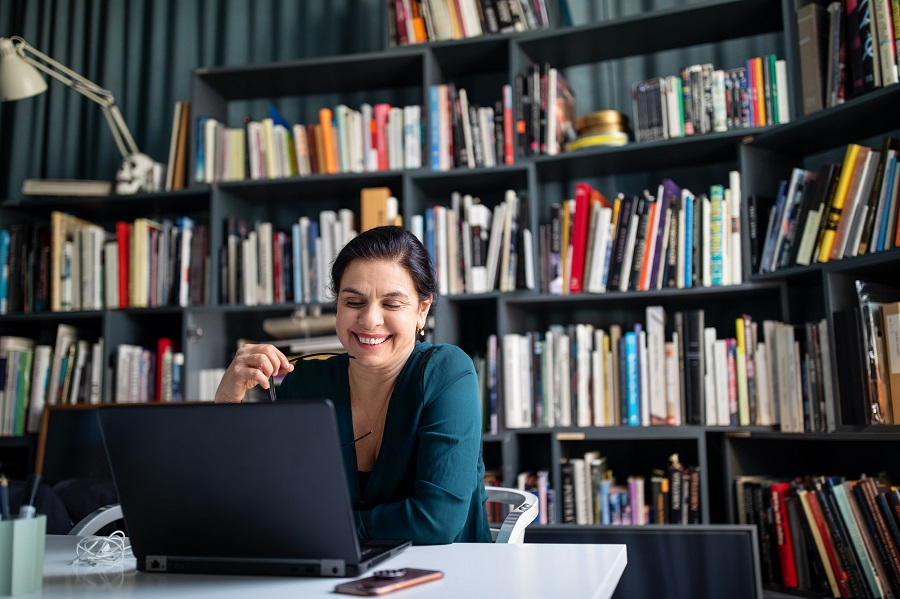 Smiling mature businesswoman using laptop at desk in workplace. Businesswoman looking at her laptop and smiling in office conference room.
