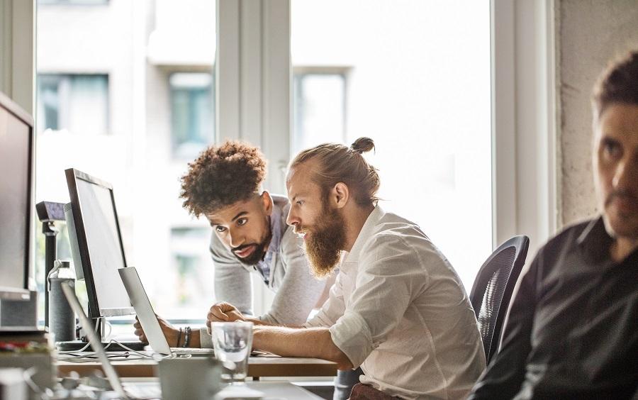 Multi-ethnic businessmen discussing over laptop in office