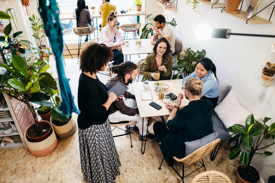 A group of people ordering at a table in a quirky café with lots of plants.