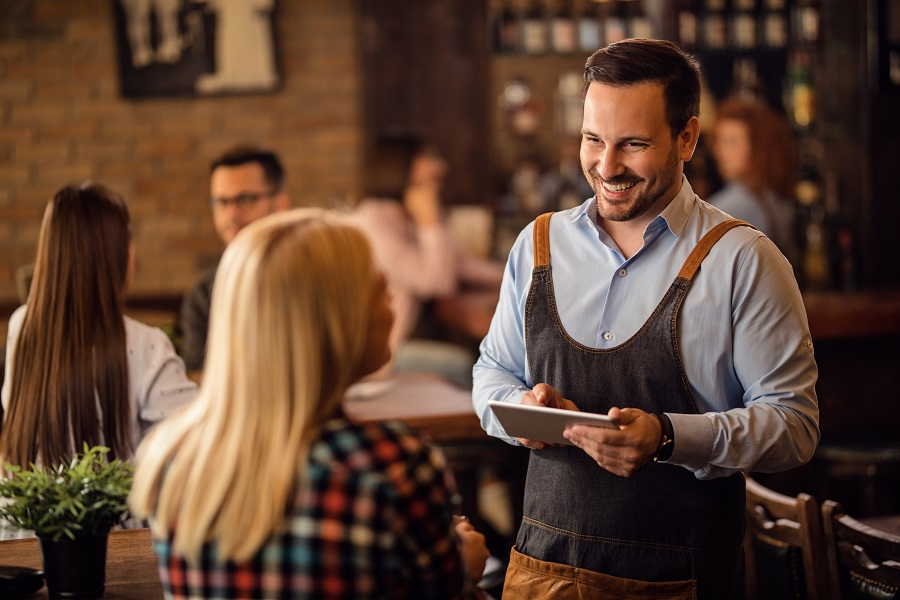 Happy waiter talking to female customer and writing her order on digital tablet in a bar.