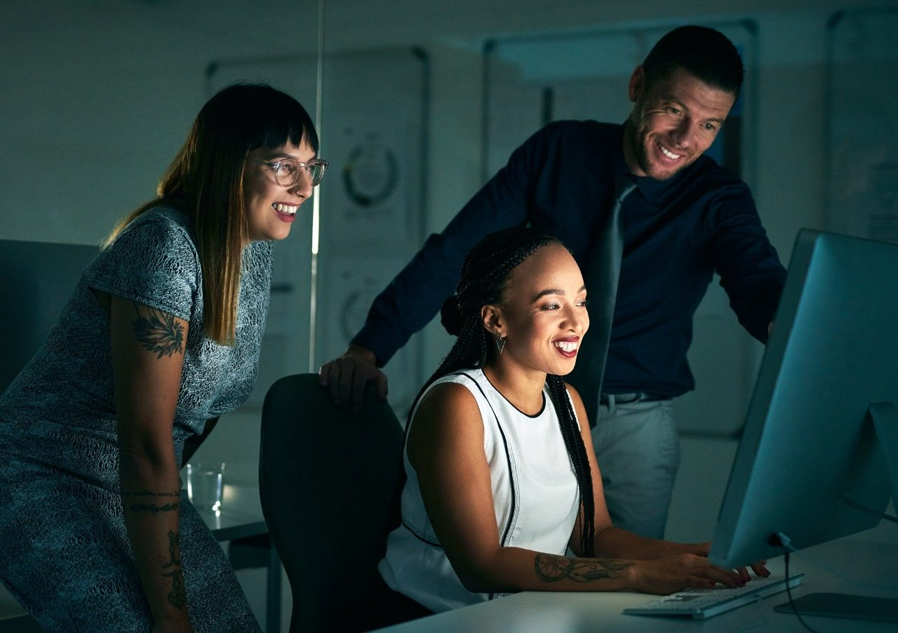Cropped shot of three business colleagues working on a computer together late at night in their office
