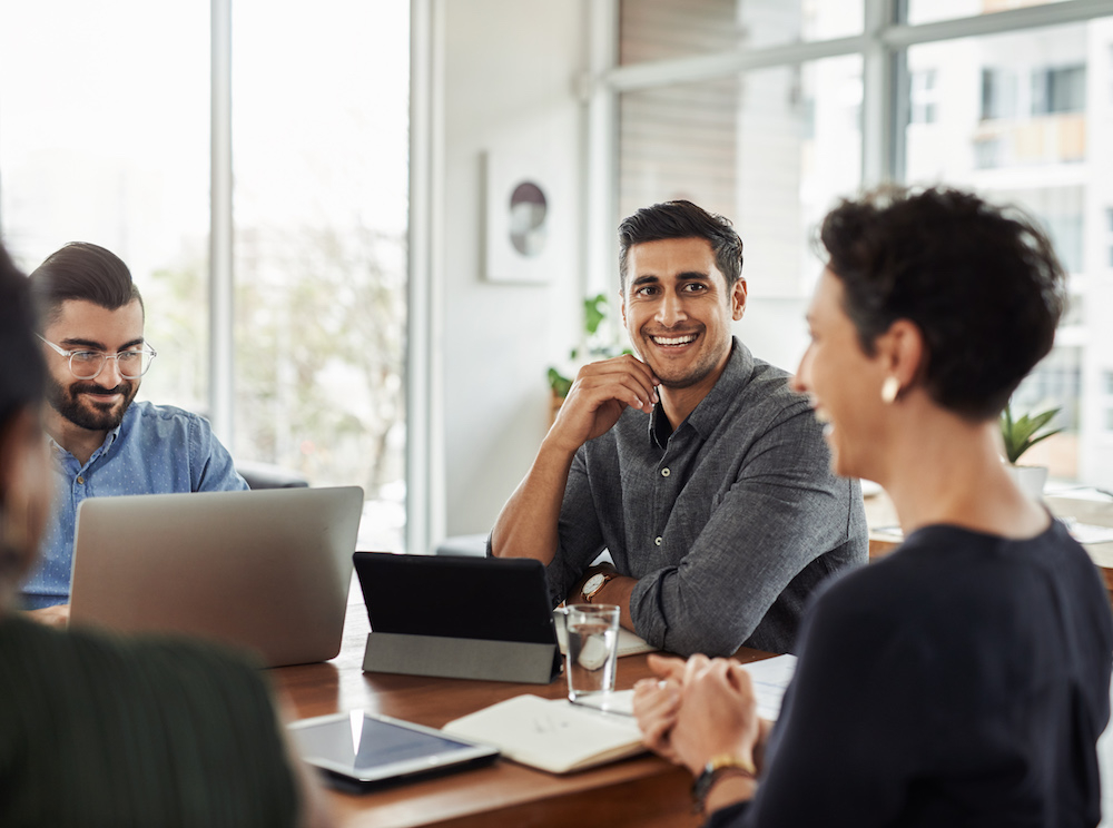 Shot of a handsome young businessman smiling during a meeting with colleagues at w