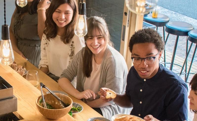 Young friends enjoying a meal at an Italian restaurant.