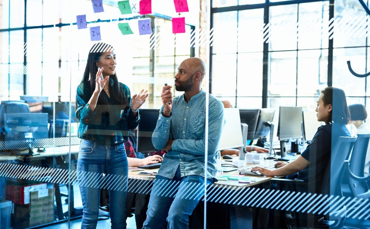 Woman female businesswoman in jeans and shirt, standing by male manager, discussing ideas in brainstorming session, planning, explaining