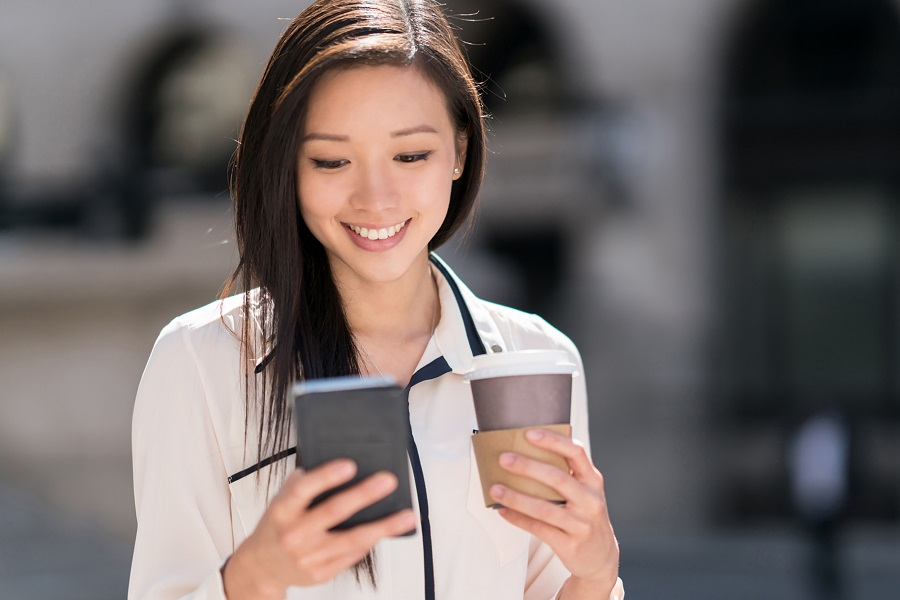 Portrait of a happy Asian business woman texting on her cell phone on the street while having a cup of coffee