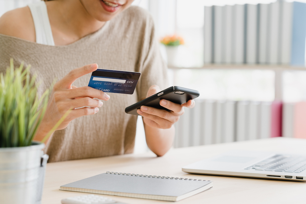 Beautiful Asian woman using smartphone buying online shopping by credit card while wear sweater sitting on desk in living room at home. Lifestyle woman at home concept. (Beautiful Asian woman using smartphone buying online shopping by credit card whil