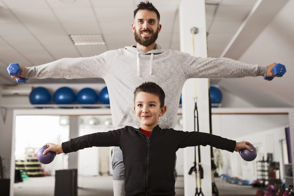 Man having fun with his son in fitness studio