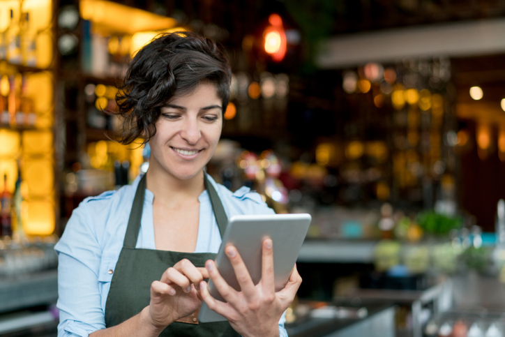 Happy waitress working at a restaurant and using app on a digital tablet