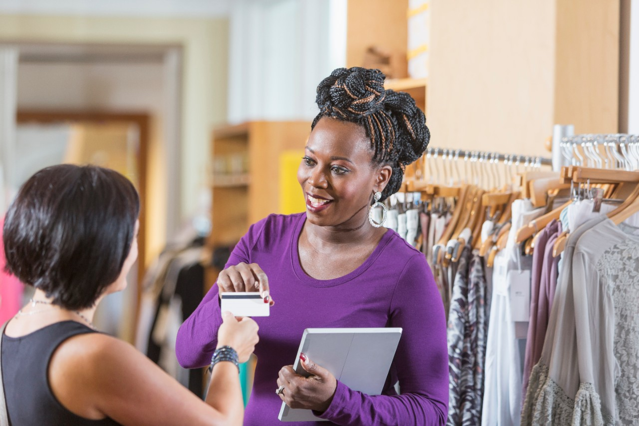 A woman working in a clothing store, taking payment from a customer. The saleswoman is holding a digital tablet, reaching for the credit card, smiling at the shopper.