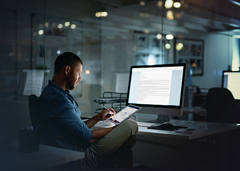 Shot of a businessman using a computer and digital tablet during a late night at the office