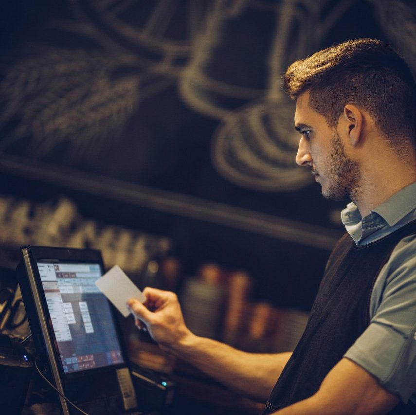 Young male waiter working at the point of sale in a bar.