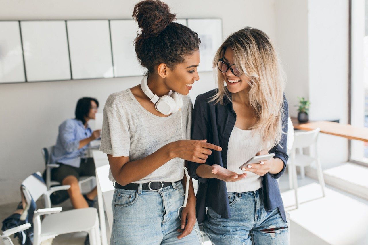 Blonde girl in jeans and glasses holding smartphone while talking with friend in office.