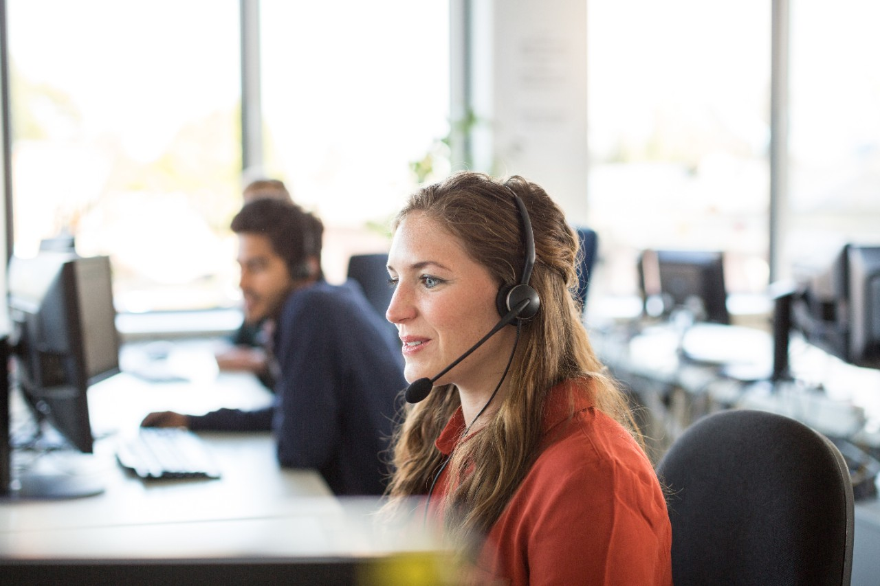 Office service employee with headset at desk happy
