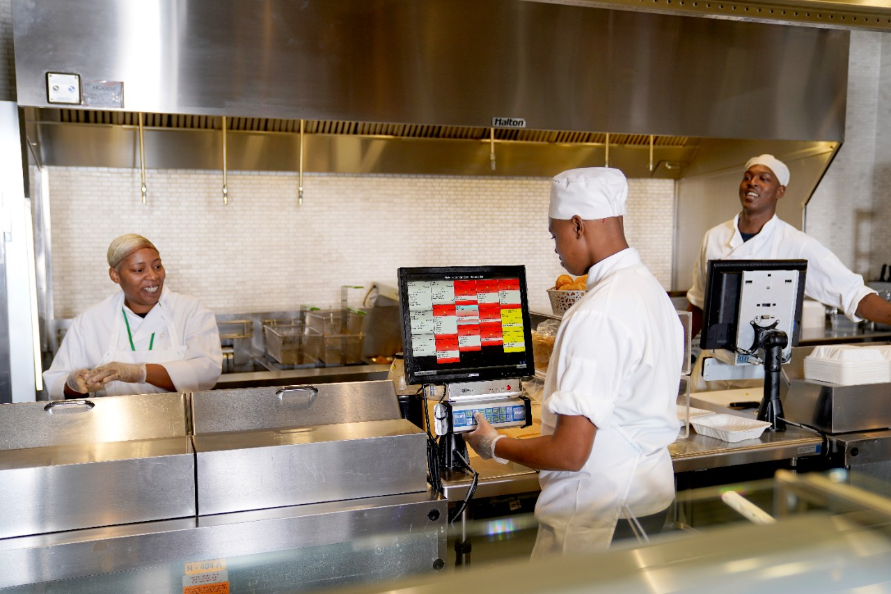 Photo of chefs cooking in kitchen using aloha kitchen software of displays