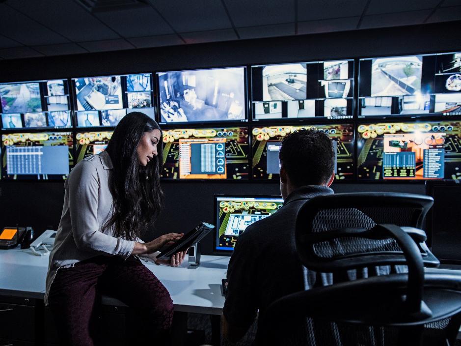 Photo of employees looking at screens of technology and security