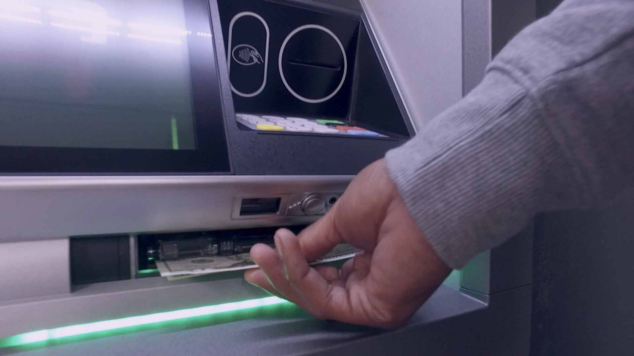 Hand reaching to get cash from ATM dispenser