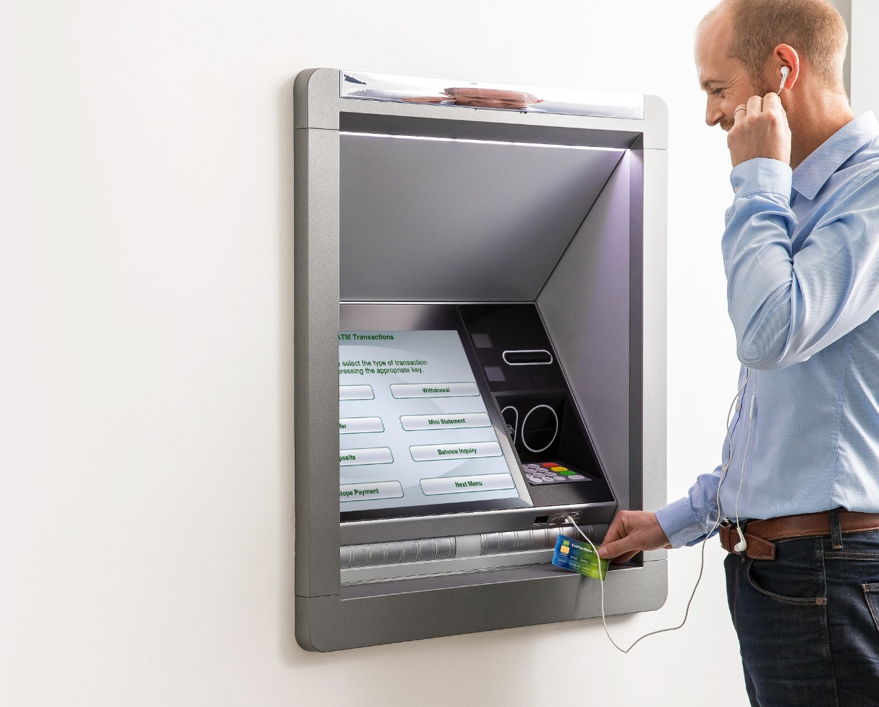 Screen showing options for ATM Transactions on NCR software on walk up ATM while a man uses his headphones and credit card to complete an action