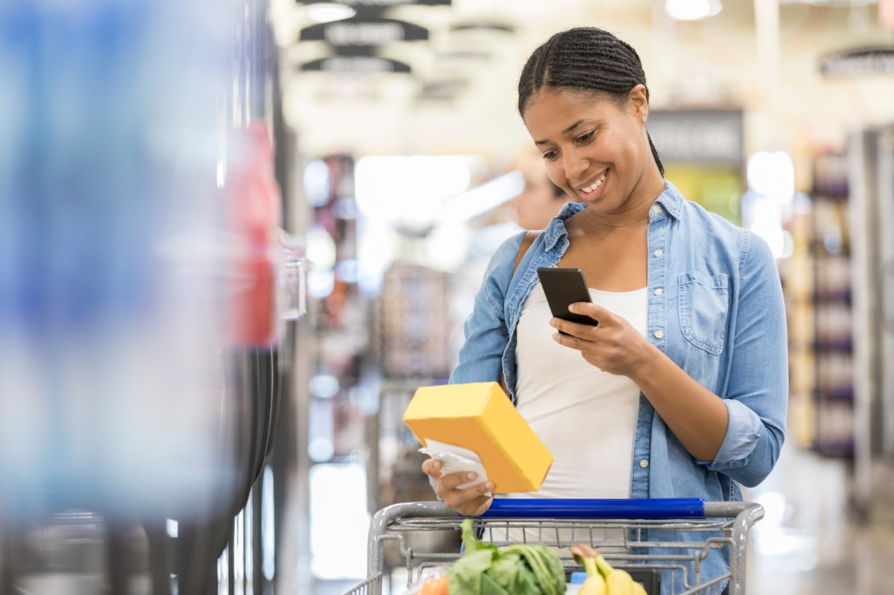 Woman uses a grocery store mobile app while shopping in a supermarket.
