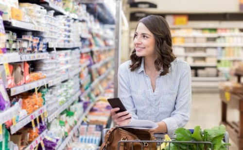 Woman shopping at grocery store and holding mobile phone