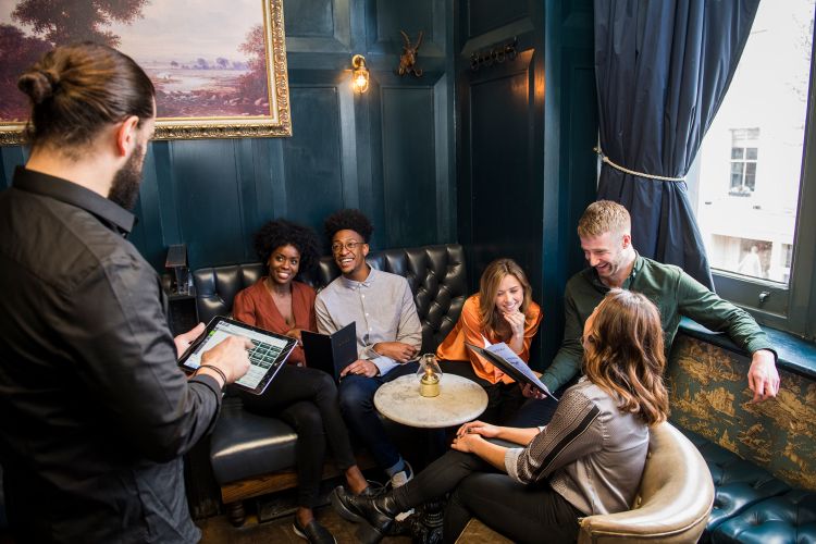 Group of friends at a restaurant ordering and waiter using tablet
