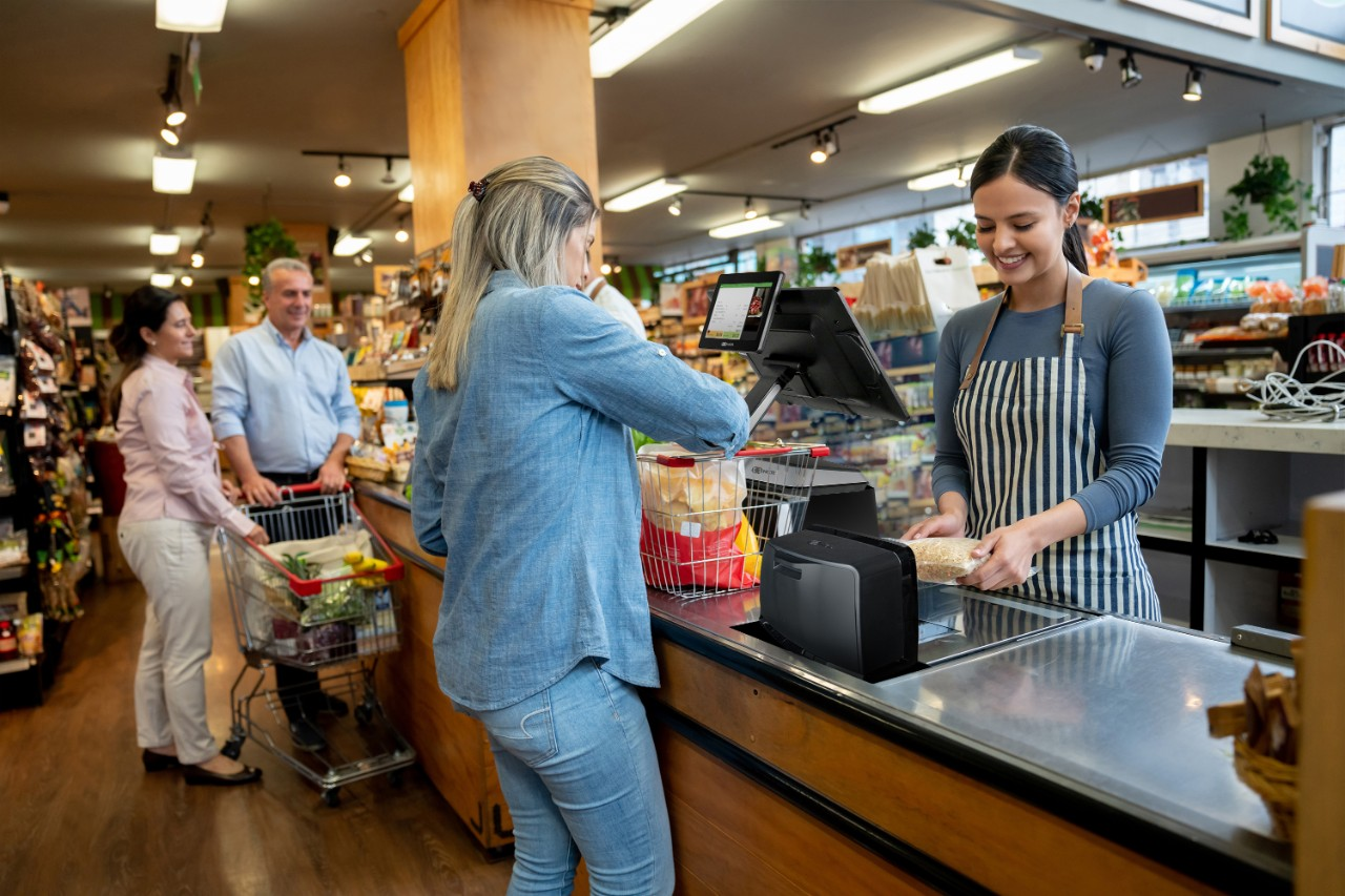 Cheerful employees at supermarket doing checkout for customers