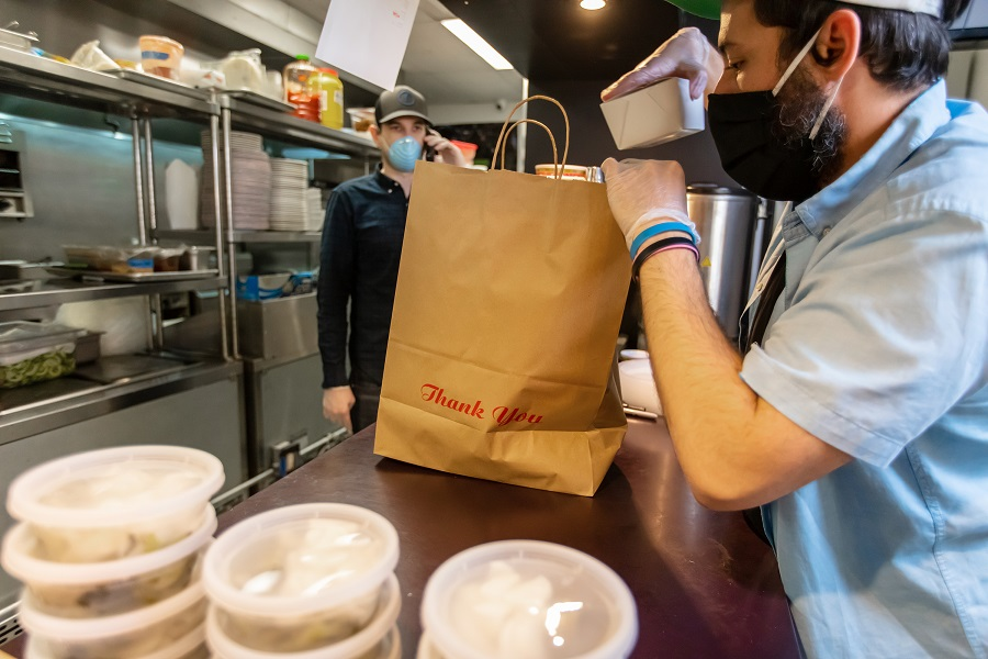 A restaurant adapts to the Covid-19 pandemic and stay at home orders by pivoting to take out and delivery.
