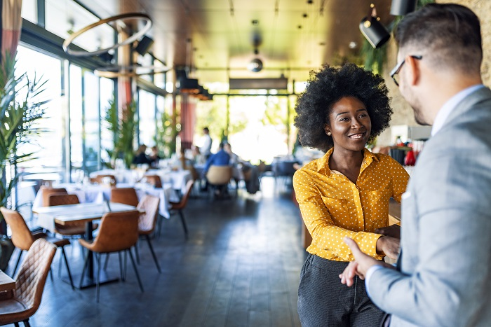 Businessman and African-American woman standing while working together at indoor cafe in informal meeting during the day.