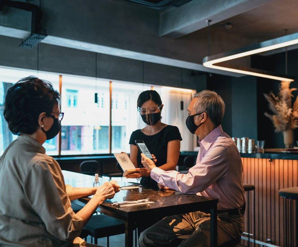 Masked couple scan QR menu at trendy restaurant in front of server