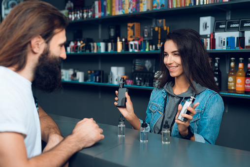 Girl seller shows the choice of electronic cigarettes in vapeshop. Nearby is a buyer - a man with a beard. The store has a large assortment of electronic cigarettes.
