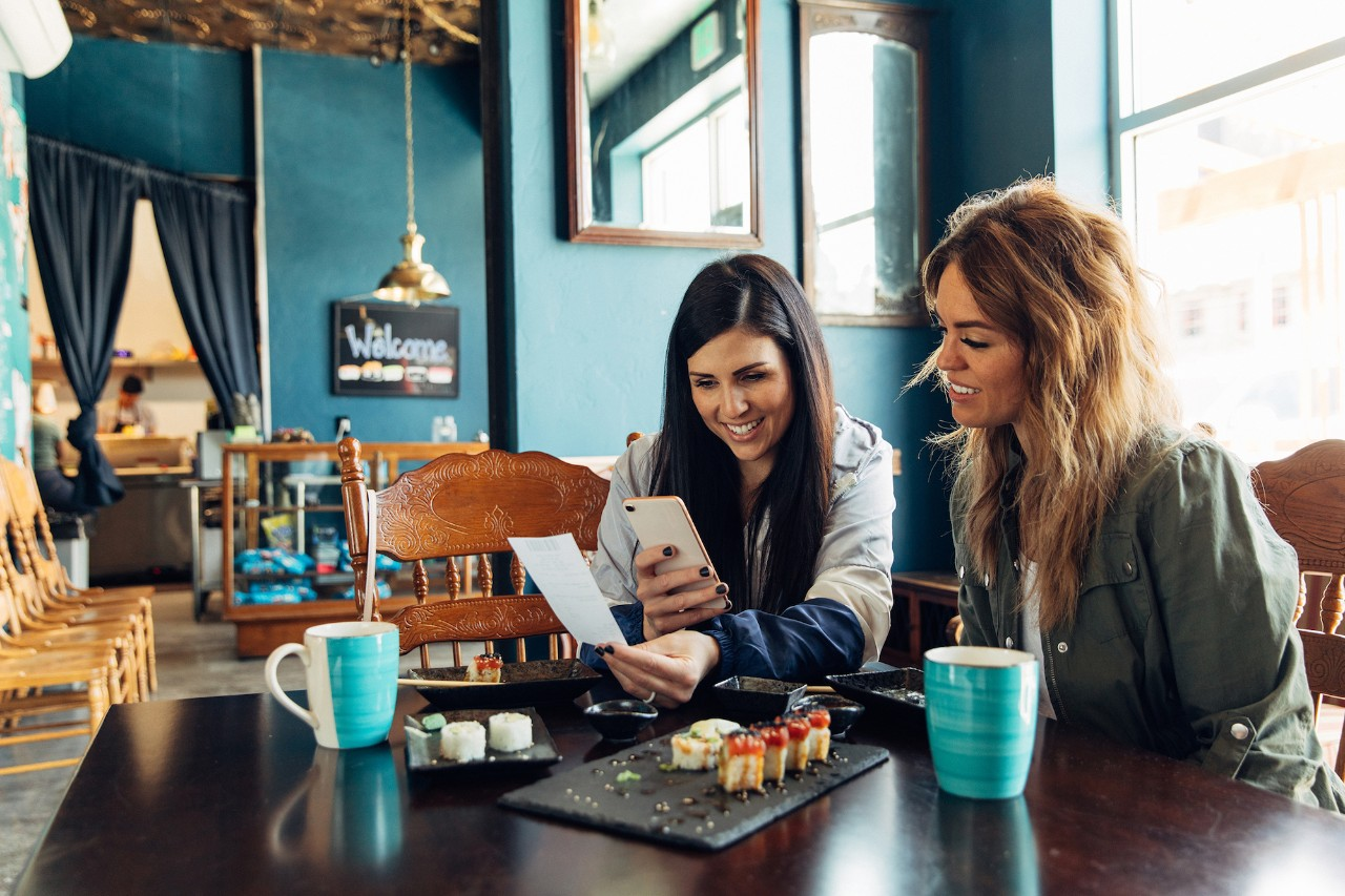 Two women of the Millennial Generation are taking a picture of a restaurant receipt after eating lunch at a local sushi restaurant. The woman is using her bank's app to balance her monthly budget. Image taken in Utah, USA.