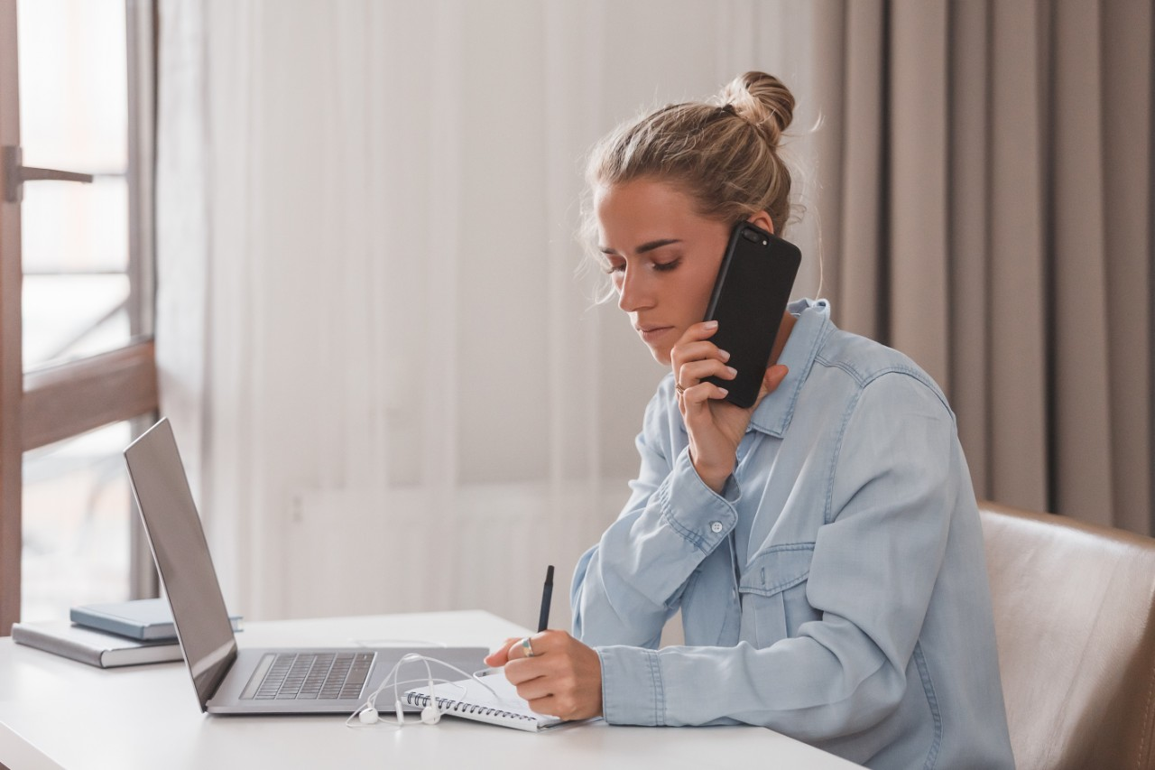 Serious attractive businesswoman agrees to an informal meeting by phone sitting at table with laptop and writing down address in notebook. Purposeful student looking for work. Career Success Concept