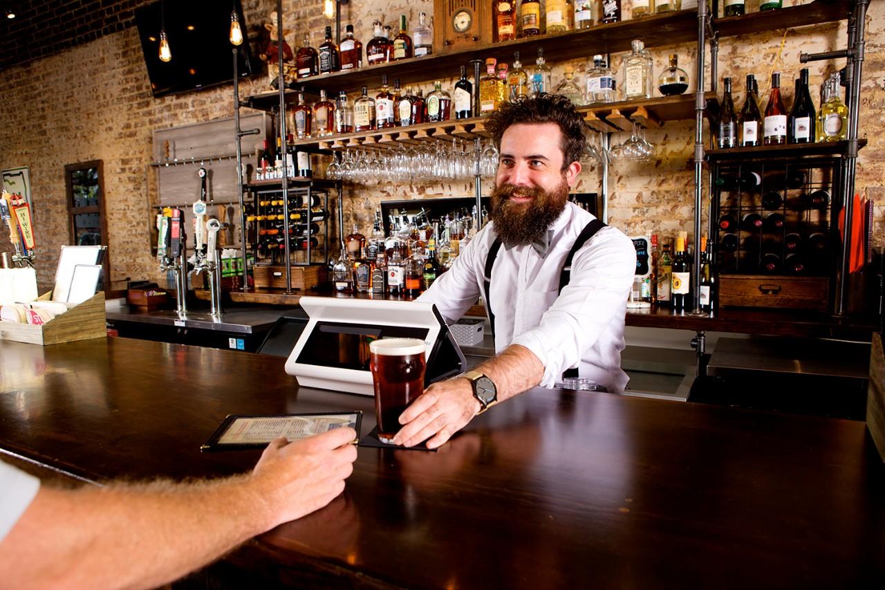 Bartender using silver quantum sliding beer across the bar to customer