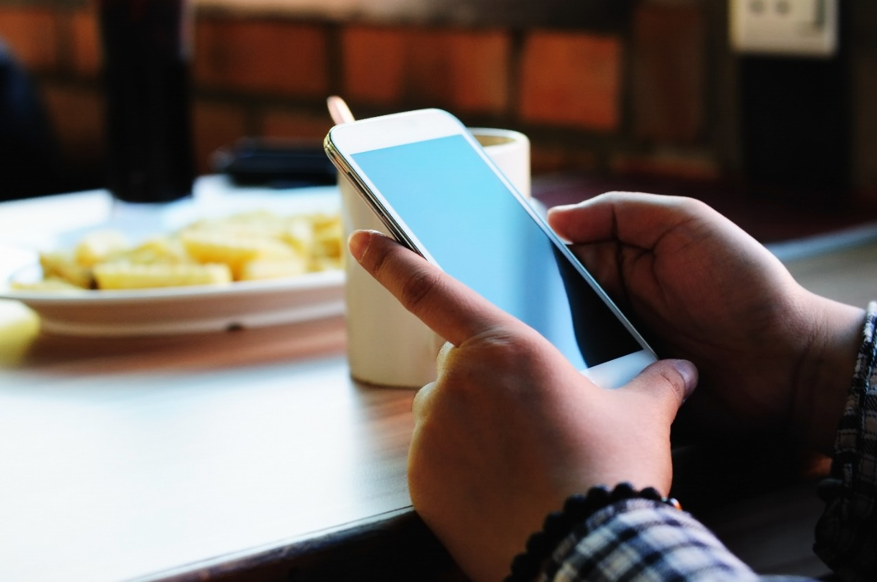 Close up of woman hands holding a smart phone at restaurant setting with cup of coffee and fries, natural light setting.