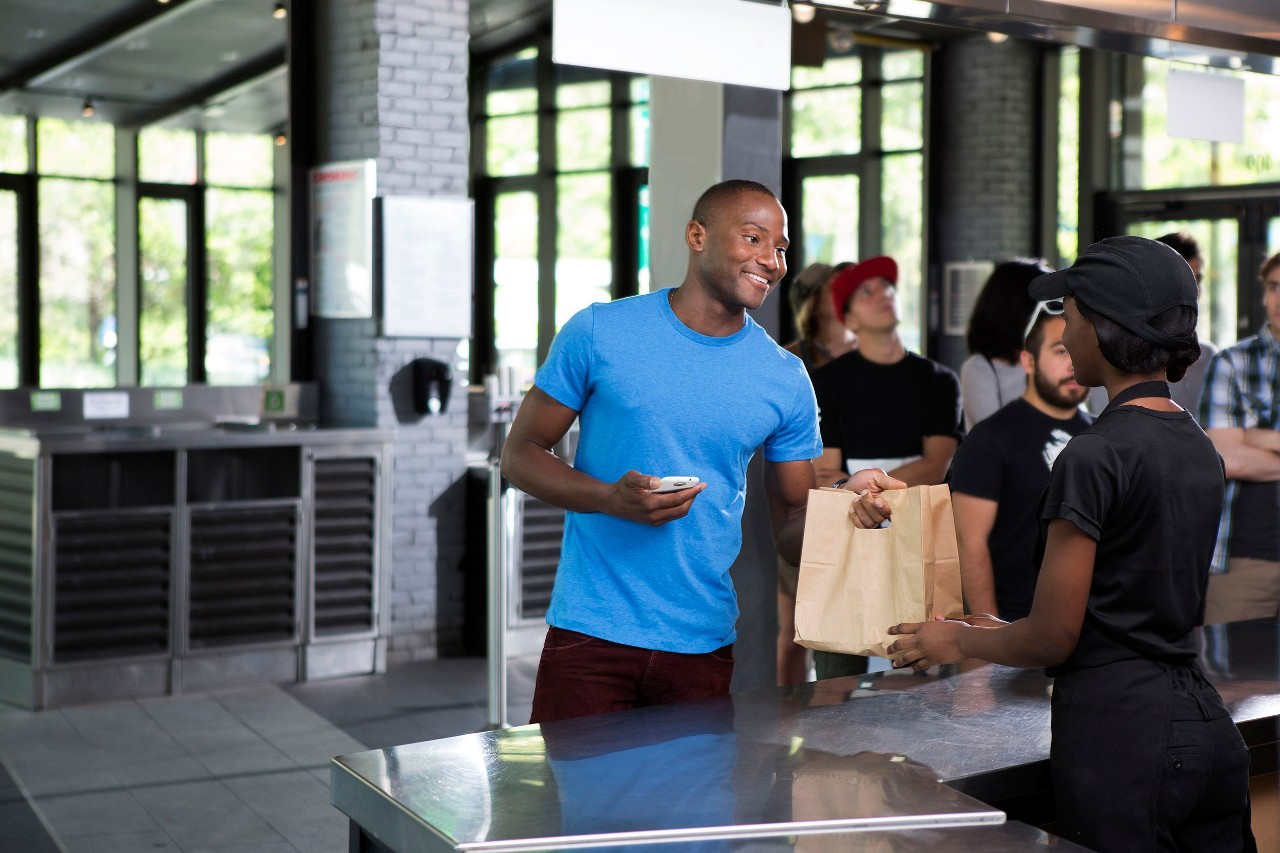 Customer picking up to go order at counter