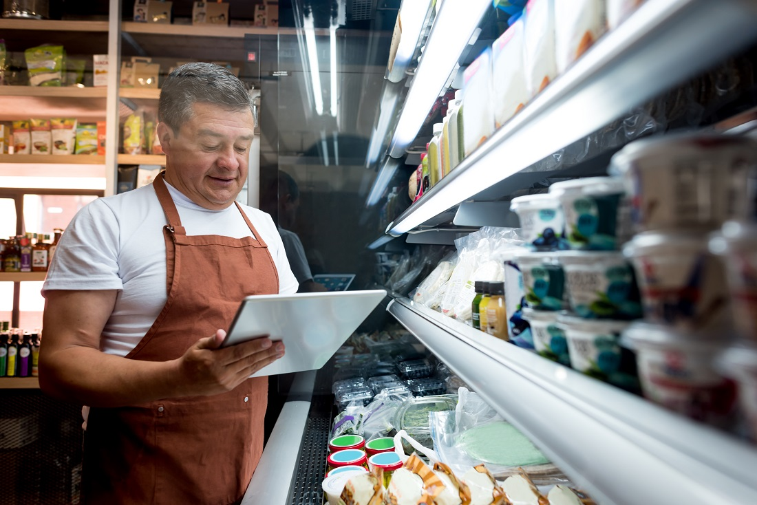 Happy man working at a grocery store doing the inventory - small business concepts